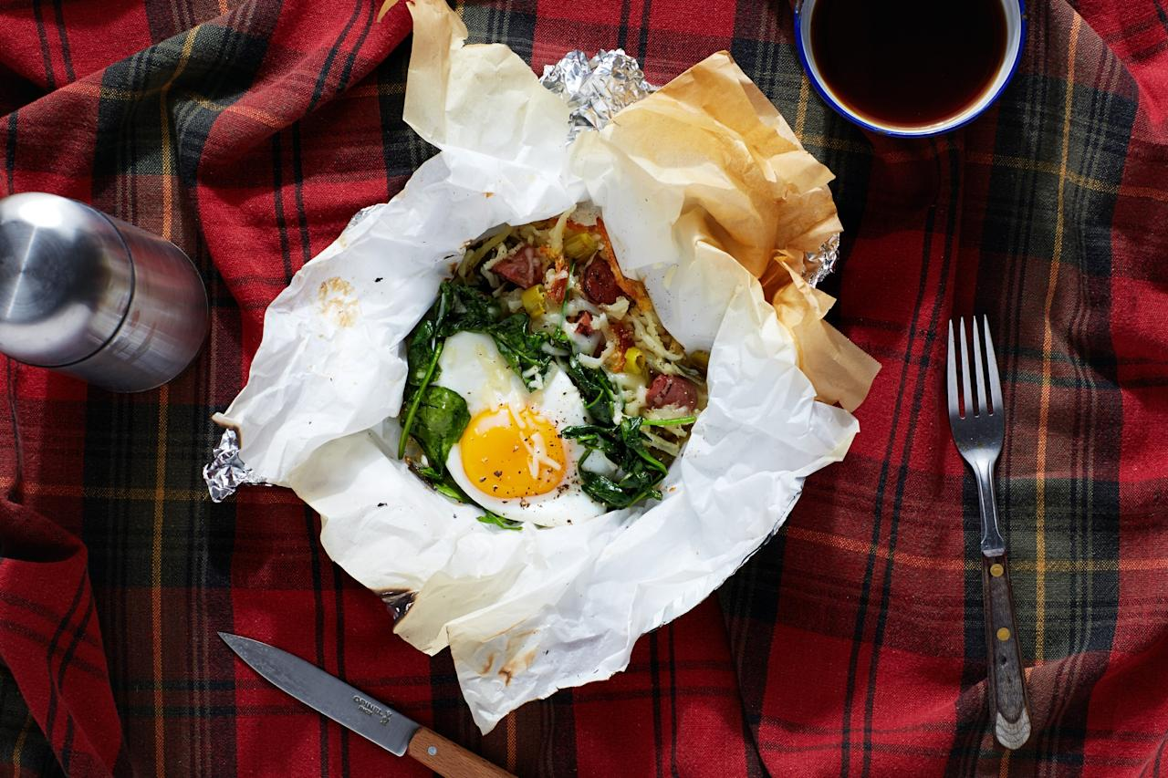 """These make-ahead packs are perfect for camping trips as well as quick and easy breakfasts on the go. Shredded potatoes and flavorful sausage are topped with baked eggs and spinach for a hearty morning meal. <a href=""""https://www.epicurious.com/recipes/food/views/breakfast-hobo-packs-with-hash-brown-potatoes-sausage-and-scallions-56389750?mbid=synd_yahoo_rss"""">See recipe.</a>"""