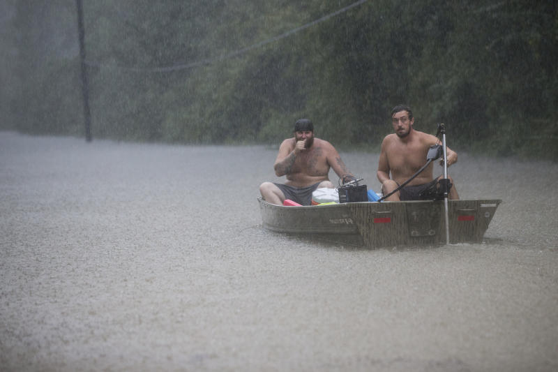 A pair of men get into a boat to float in to rescue a family trapped by floodwaters as rain from Tropical Depression Imelda inundated the area on Thursday, Sept. 19, 2019, near Patton Village, Texas. (Brett Coomer/Houston Chronicle via AP)