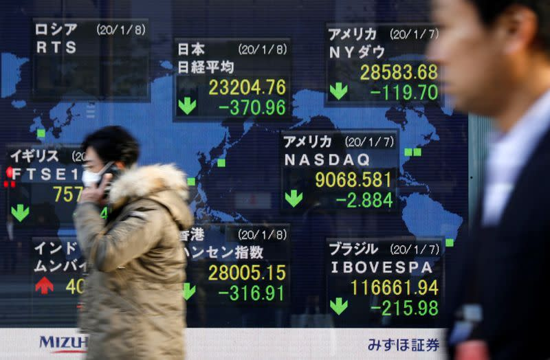 People walk past an electronic display showing world markets indices outside a brokerage in Tokyo