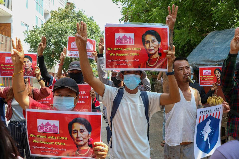 <p>Anti-coup protesters flash the three-fingered symbol of resistance while holding slogans bearing pictures of deposed leader Aung San Suu Kyi during a demonstration in Yangon, Myanmar on Wednesday 7 April</p> (AP Photo)
