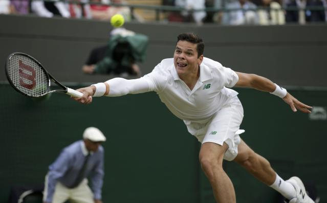Milos Raonic of Canada hits a return during his men's singles quarter-final tennis match against Nick Kyrgios of Australia at the Wimbledon Tennis Championships, in London July 2, 2014. REUTERS/Max Rossi (BRITAIN - Tags: SPORT TENNIS TPX IMAGES OF THE DAY)