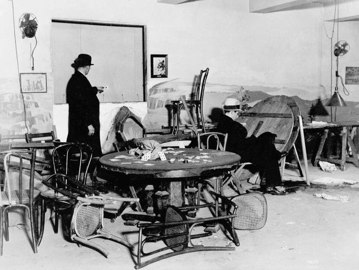"FILE - In this Dec. 31, 1931, file photo the wrecked speakeasy in the Hotel Victoria in mid-Manhattan, where Louis Levine, alias Louis Taylor, a small-time gambler, was killed by one of three gunmen earlier in the day in New York. A bystander points to a bullet hole in the wall, while another is seated in the chair where Levine, known as ""Crooked Neck Louie"", was gambling when he was shot. (AP Photo, File)"
