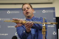 Brian Haight, crane program manager for Washington state's Department of Labor and Industries, uses a model of a crane during a news conference to explain the collapse of a crane earlier in the year in Seattle that killed four, Thursday, Oct. 17, 2019, in Tukwila, Wash. Washington state's L&I released the results of its investigation on the collapse Thursday. It found, as experts have long suspected, that the crane toppled because workers who were disassembling it had prematurely removed pins securing the sections of the crane's mast. (AP Photo/Elaine Thompson)