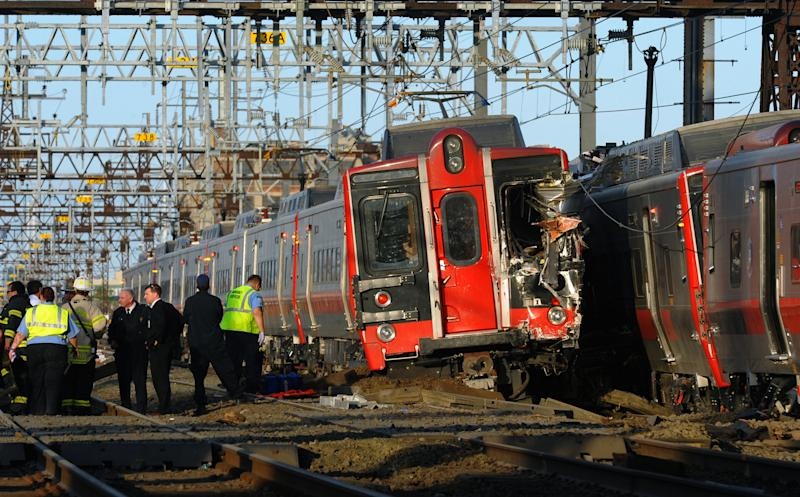 "FILE - In this May 17, 2013 file photo, emergency workers arrive at the scene of a train collision in Fairfield, Conn, after two Metro-North commuter trains serving New York City collided during Friday's evening rush hour. According to a Federal Railroad Administration review prompted by another accident on Dec. 1, 2013 that killed four passengers and injured about 70 others, the Metro-North commuter railroad has allowed its emphasis on trains' on-time performance to ""routinely"" overshadow its safety operations. (AP Photo/The Connecticut Post, Christian Abraham, File) MANDATORY CREDIT"