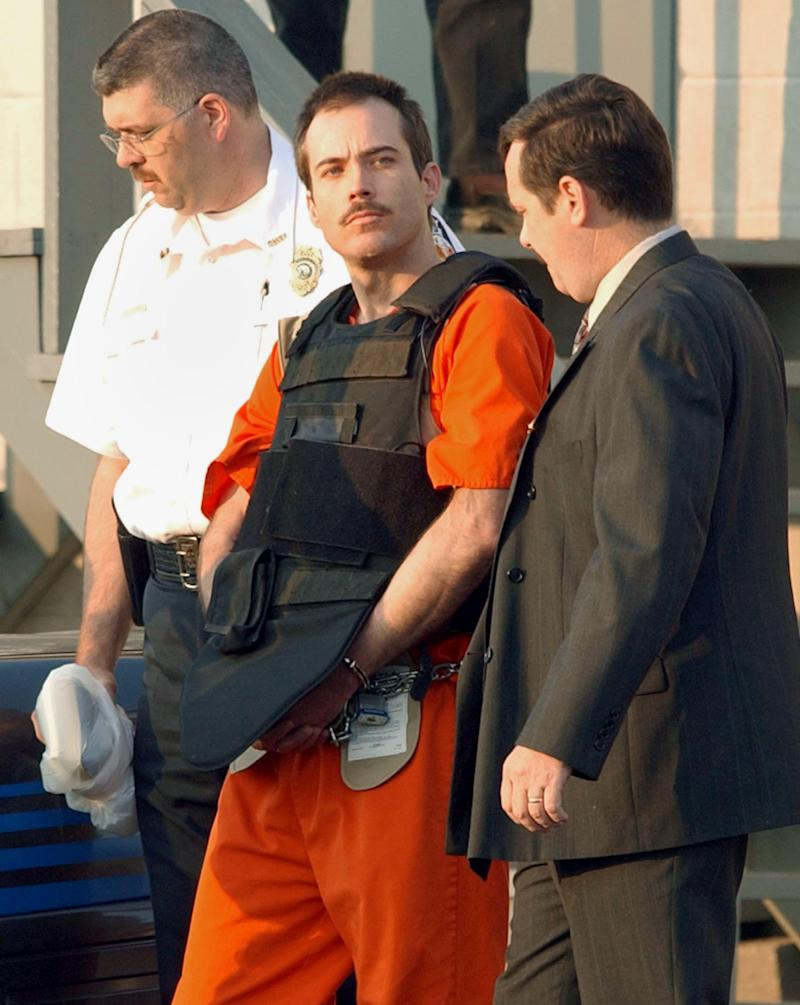 MURPHY, NORTH CAROLINA - JUNE 2: Multiple bombing suspect Eric Robert Rudolph (C) is escorted by law enforcement officials from the Cherokee County Courthouse and Jail in Murphy, North Carolina, June 2, 2003 to a Federal court hearing in Asheville, North Carolina. Rudolph is a suspect in at least three bombings, including the 1996 Olympic Park bombing in Atlanta. (Photo by Erik S. Lesser/Getty Images)