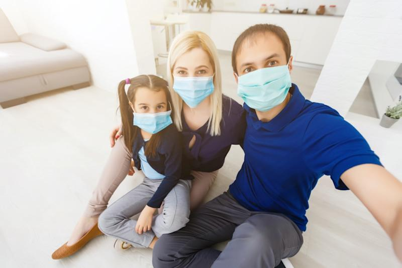 family with dad, mom and daughter staying at home wearing facial masks