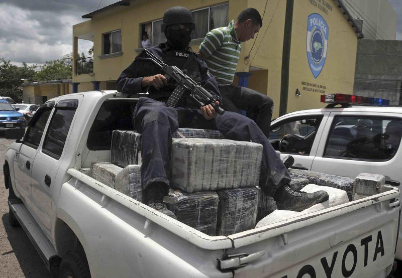 FILE - In this Tuesday July 3, 2012 file photo,  a Honduras national policeman sits on packages of cocaine that were brought to Tegucigalpa, Honduras. The cocaine was seized from a small airplane that crashed after it was being chased by military planes and helicopters of the Honduras army near the town of Los Lirios, about 217 miles (350 km) east of Tegucigalpa. Three-quarters of all U.S.-bound cocaine passes through Honduras, an illicit business that has led to an explosion of violence.  Honduras has more murders than any other country in the world, says the World Health Organization.(AP Photo/Fernando Antonio, file)