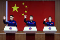 In this photo released by Xinhua News Agency, Chinese astronauts, from left, Ye Guangfu, Zhai Zhigang and Wang Yaping wave to reporters as they arrive for a press conference at the Jiuquan Satellite Launch Center ahead of the Shenzhou-13 launch mission from Jiuquan in northwestern China, Thursday, Oct. 14, 2021. China is preparing to send three astronauts to live on its space station for six months — a new milestone for a program that has advanced rapidly in recent years. (Ju Zhenhua/Xinhua via AP)