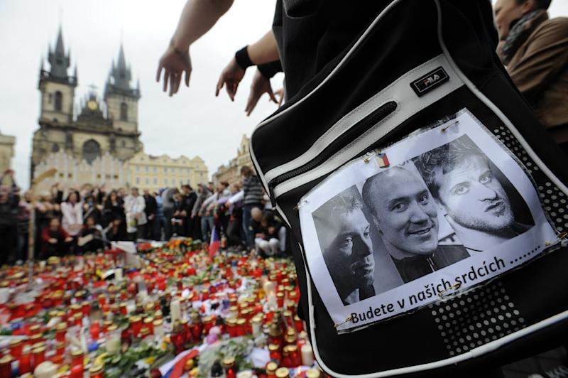 People gather at Old Town Square in Prague, Czech Republic, on Thursday, Sept. 8, 2011, to pay tribute to the Lokomotiv Yaroslavl players including three Czechs - Josef Vasicek, Karel Rachunek and Jan Marek (seen from left to right on a poster at right side of the picture) -  killed in a plane crash in the city of Yaroslavl the day before. The Old Town Square is the place where Czech hockey players usually celebrate their successes with fans. The Yak-42 jet carrying the Lokomotiv ice hockey team crashed while taking off Wednesday near Yaroslavl, on the Volga River about 150 miles (240 kilometers) northeast of Moscow, Russia, killing 43 people.  Words in Czech on the poster read: We will keep you in our hearts. (AP Photo/CTK, Michal Kamaryt) SLOVAKIA OUT -