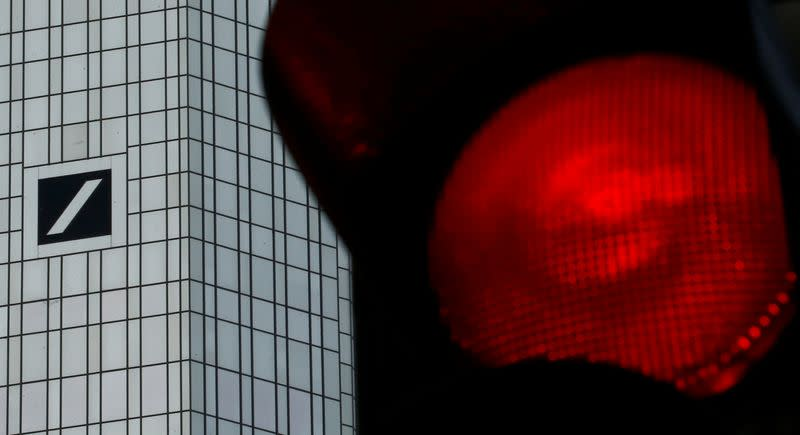 FILE PHOTO: A red traffic lights is seen next to the headquarters of Germany's Deutsche Bank in Frankfurt