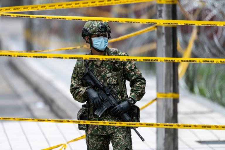 A soldier stands in front of a Kuala Lumpur apartment block cordoned off due to a number of coronavirus cases (AFP Photo/Mohd RASFAN)