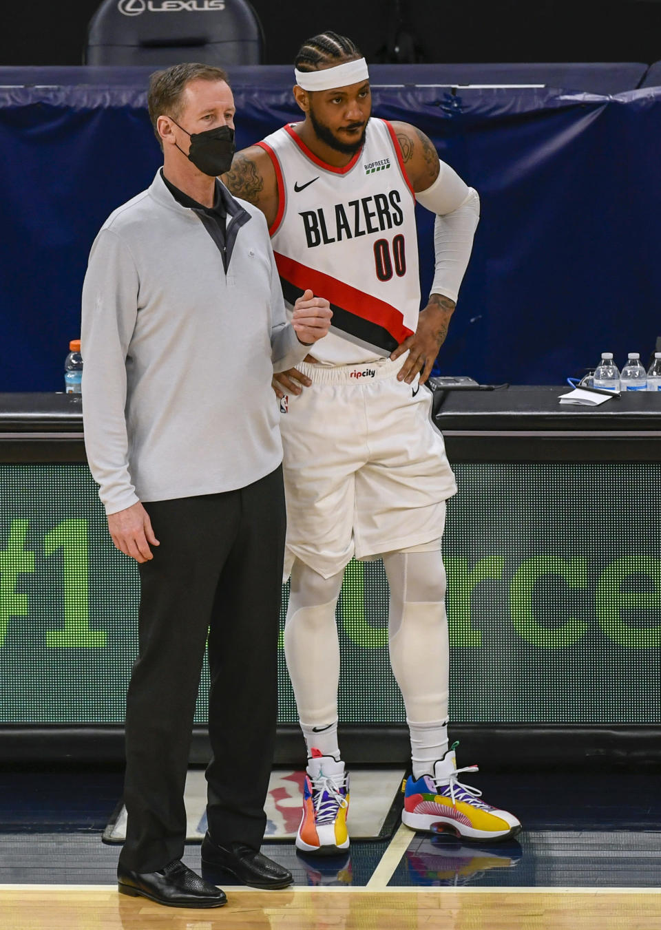 Portland Trail Blazers coach Terry Stotts, left, talks with forward Carmelo Anthony during a stop in play in the second half of the team's NBA basketball game against the Minnesota Timberwolves on Saturday, March 13, 2021, in Minneapolis. (AP Photo/Craig Lassig)