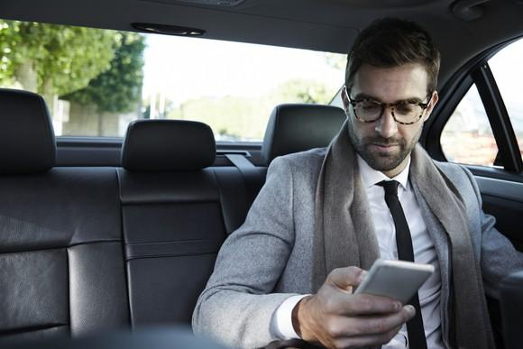 A businessman in the back of a taxicab, looking at his smartphone