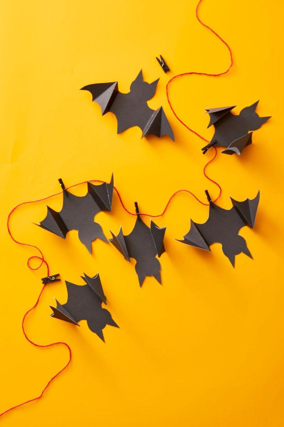 "<p>Give their bedroom a holiday makeover by draping this paper garland over their door frame, windows, or shelves. To make, download <strong><a href=""https://hmg-prod.s3.amazonaws.com/files/ghkhalloween-batgarland-1564764043.pdf"" rel=""nofollow noopener"" target=""_blank"" data-ylk=""slk:this bat stencil"" class=""link rapid-noclick-resp"">this bat stencil</a></strong>, then trace the shape onto a piece of black craft paper and cut out the bat with scissors. Place the stencil back atop each critter you create and use a bone folder to make creases along the dotted lines on the stencil. Fold the creases opposite ways on each wing to make the wings 3D. Attach each bat to a long piece of string with tiny black clothespins.</p>"