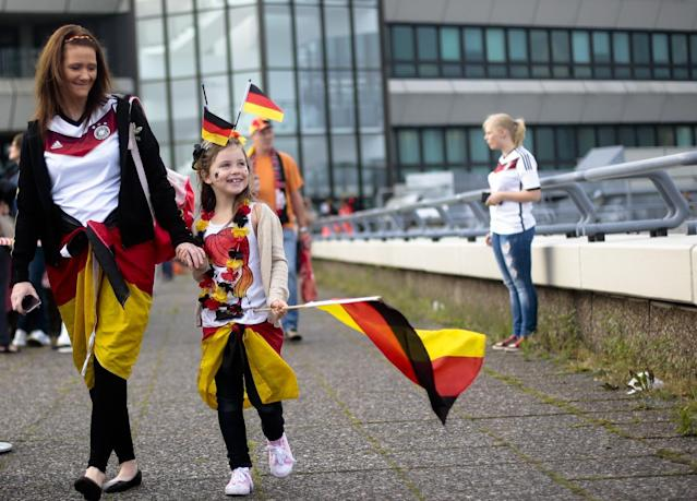 Seven years old girl Charleen, center, arrives at the airport Tegel to welcome German national soccer team in Berlin Tuesday, July 15, 2014. Germany beat Argentina 1-0 on Sunday to win its fourth World Cup title. (AP Photo/Markus Schreiber)