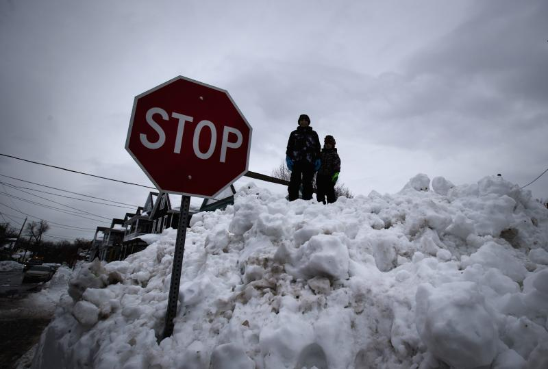 Children play on top of a giant snow pile following a massive snow storm in Buffalo