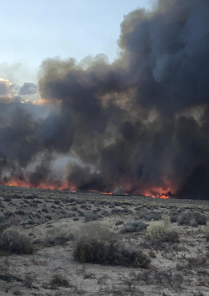This Sunday, Feb. 18, 2018 photo released by the Inyo County Sheriff's Office shows smoke rising from wildfires near Bishop, Calif. A wind-driven wildfire in rural central California forced mandatory evacuations and threatened hundreds of buildings Monday, including a historic railroad station, after it tripled in size overnight, officials said. (Inyo County Sheriff's Office via AP)