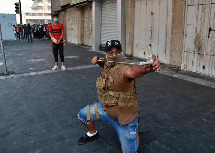 A protester uses a slingshot to fire a stone at security forces, in downtown Baghdad, Iraq, Sunday, Nov. 10, 2019. On Sunday, Amnesty International called on Iraqi authorities to immediately rein in security forces after at least six protesters were killed in central Baghdad amid a widening security crackdown. The deaths, including five by live ammunition, occurred Saturday during a police operation to clear demonstrations from several bridges and streets near Tahrir Square, the epicenter of the protests. (AP Photo/Khalid Mohammed)