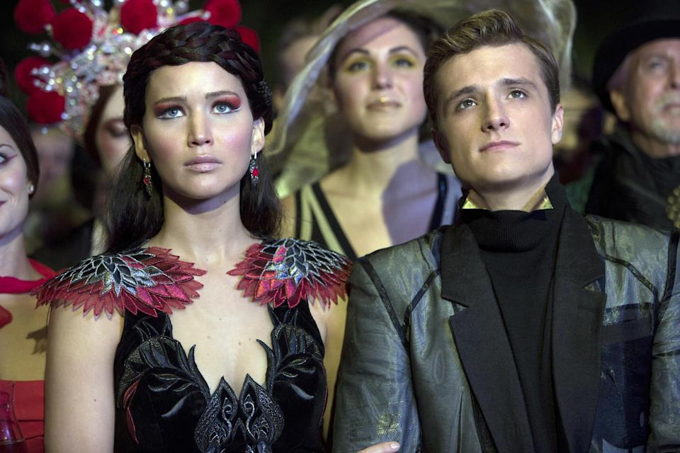 katniss and peeta sitting in a crowd together