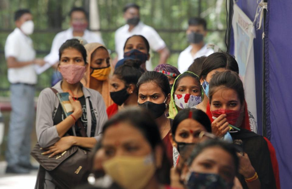 A group of women wearing masks line up to get vaccinated against COVID-19.