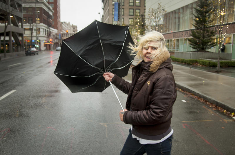 During a strong gust of wind, Michele Purkey's umbrella flips back as she crosses the intersection of First Avenue and Wall Street on Monday, Nov. 19, 2012, in downtown Spokane, Wash. Residents in Washington and Oregon are bracing for expected river flooding after heavy rain and winds that caused sporadic road closures, power outages and at least one death. The wet weather is expected to continue throughout the week, after hurricane-strength winds battered both states along the coast. (AP Photo/The Spokesman-Review, Colin Mulvany)
