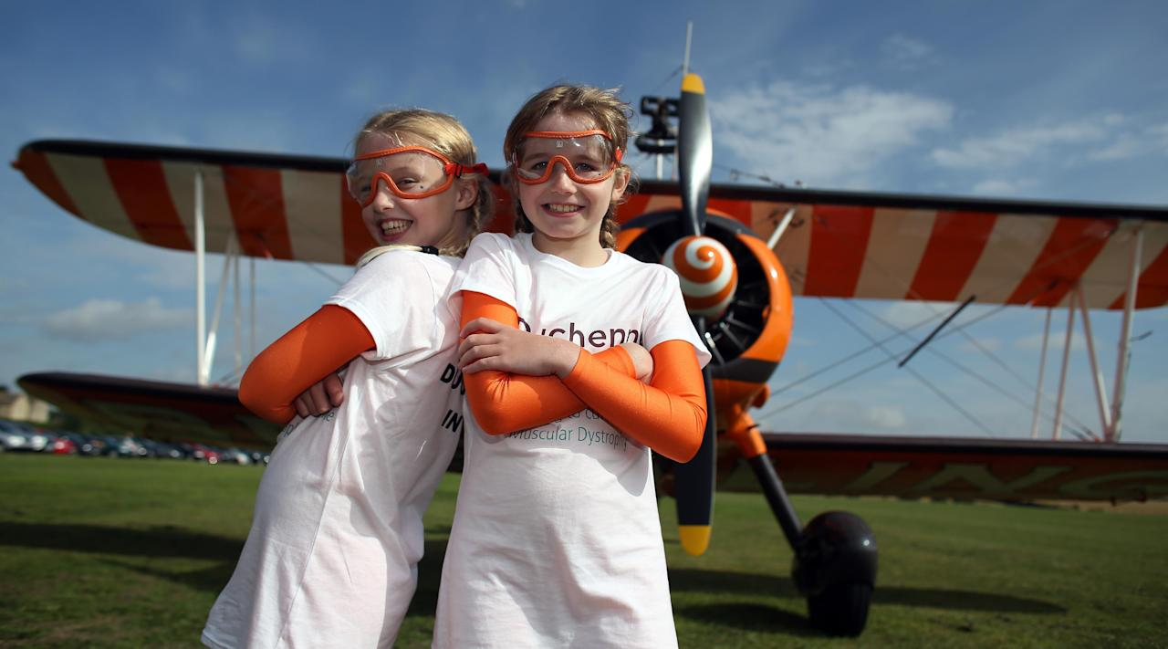 Nine-year-old cousins Rose Powell (left) and Flame Brewer prepare to go wing-walking over Rendcomb Airfield near Cirencester for the charity Duchenne Children's Trust.
