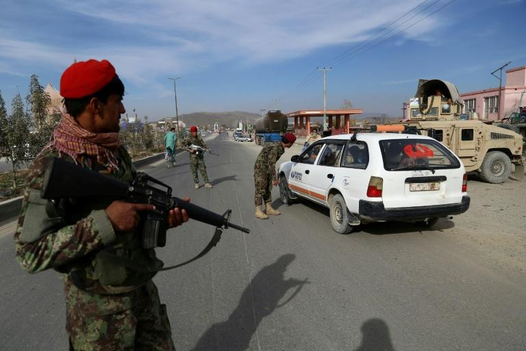 Afghan security personnel search passengers at a highway checkpoint in Ghazni, capital of the restive Ghazi province