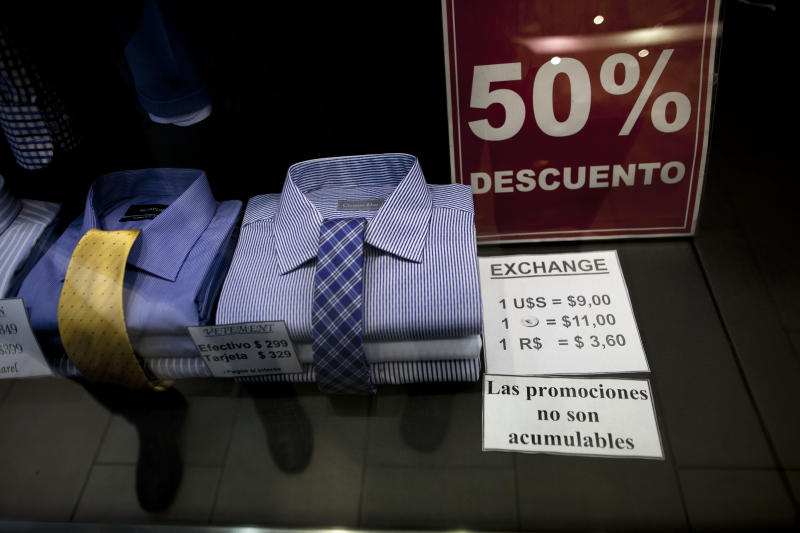 "In this June 5, 2013 photo, a shop window displays a sign that reads in Spanish ""50% discount"" as well as the store's accepted rates of exchange in the informal market for the Argentine peso with the US dollar, the euro, and Brazil's real, along Florida street in Buenos Aires, Argentina. The weakening peso has led to a flood of day-trippers from neighboring countries into Argentina, which imposed severe currency controls in hopes of reducing the flight of dollars and protecting foreign reserves. (AP Photo/Natacha Pisarenko)"