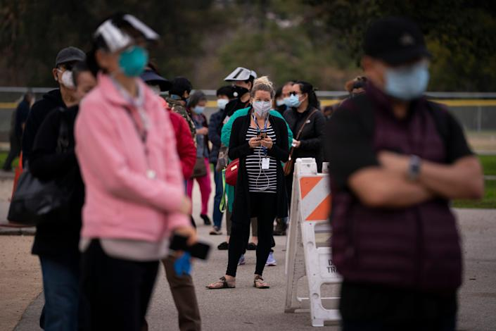 People wait in line to get COVID-19 vaccinations on Tuesday in a park in the Lincoln Heights neighborhood of Los Angeles.