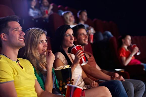 A group of young people at a movie theater drinking soda and eating popcorn.