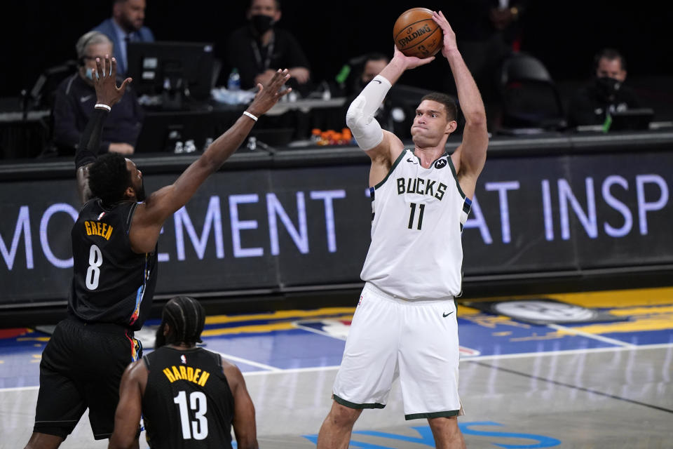 Milwaukee Bucks center Brook Lopez (11) shoots over Brooklyn Nets forward Jeff Green (8) and guard James Harden (13) during the first half of Game 5 of a second-round NBA basketball playoff series Tuesday, June 15, 2021, in New York. (AP Photo/Kathy Willens)