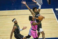Miami Heat forward Jimmy Butler, center, goes up for a shot past Minnesota Timberwolves forward Jaden McDaniels, right, and forward Josh Okogie during the first half of an NBA basketball game Friday, April 16, 2021, in Minneapolis. (AP Photo/Craig Lassig)