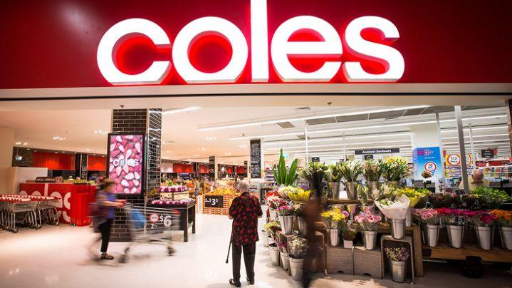 Photo shows the entryway to a Coles supermarket including a display of fresh flowers for sale, with an elderly woman standing in front of it.