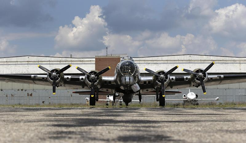 """The B-17G """"Yankee Lady"""" is shown in front of the old Willow Run Bomber Plant at Willow Run Airport in Ypsilanti Township, Mich., Wednesday, July 17, 2013. The bomber plant west of Detroit was where, at President Franklin Roosevelt's urging, Ford Motor Co. switched from making cars to planes and produced one an hour _ nearly 9,000 B-24 Liberator bombers in all _ to help win the war in Europe. At the time of its 1940s construction, the plant was the largest factory in the world, employing 40,000 men and women, including Rose Will Monroe, who was believed to have been the inspiration for the famed Rosie the Riveter character. The factory went back to auto production for half a century under the General Motors name and closed for good last decade. The plan is to knock it down. But a group of donors are hoping to save at least a piece of it so they can erect a museum dedicated to Detroit's role as the """"Arsenal of Democracy."""" To make that happen, though, organizers need to raise $5 million by Aug. 1. (AP Photo/Paul Sancya)"""