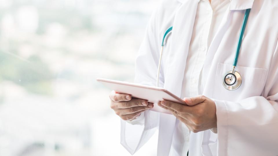 Medical doctor or physician holding mobile tablet for patient's health record in clinic or hospital office for professional online and emergency healthcare assistance service concept