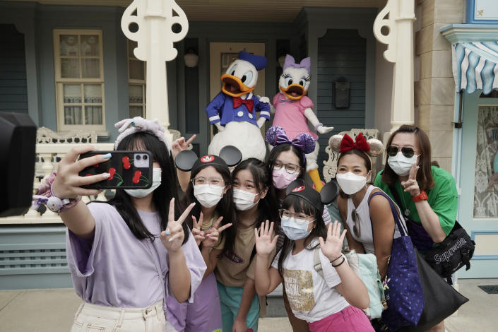 Visitors wearing face masks take a selfie with the iconic cartoon characters Donald Duck and Daisy Duck at the Hong Kong Disneyland, Friday, Sept. 25, 2020. Hong Kong Disneyland reopened its doors to visitors after closed temporarily due to the coronavirus outbreak. (AP Photo/Kin Cheung)