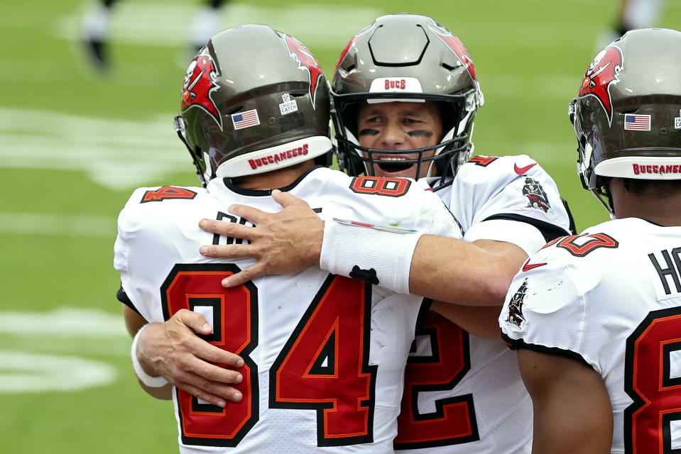 Tom Brady smiles while hugging Cameron Brate.