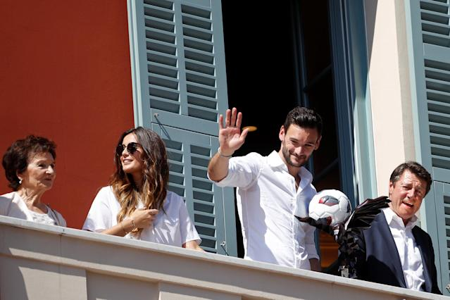France soccer team goalkeeper Hugo Lloris surrounded by his wife Marine, and Christian Estrosi, Mayor of Nice, waves to the crowd from a balcony at the city hall in Nice, after their victory in the 2018 Russia Soccer World Cup, in Nice, France, July 18, 2018. REUTERS/Eric Gaillard