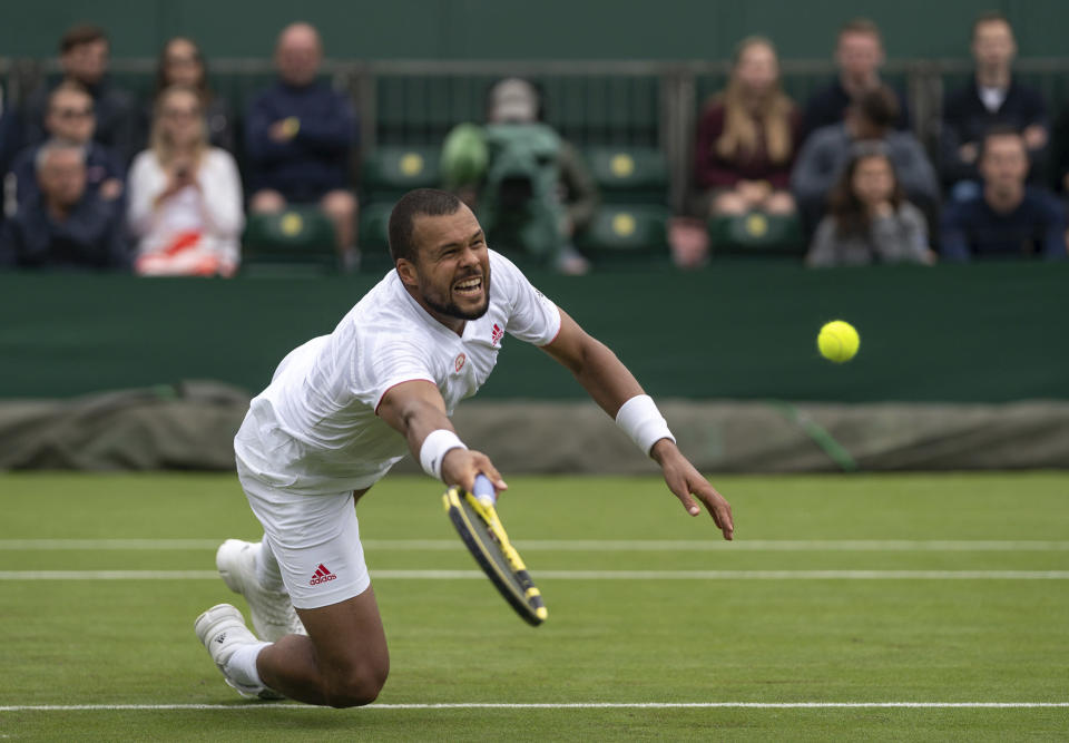 Jo-Wilfried Tsonga of France reaches for a volley as he plays against Sweden's Mikael Ymer during the men's singles first round match on day three of the Wimbledon Tennis Championships in London, Wednesday June 30, 2021. (Jed Leicester/Pool via AP)