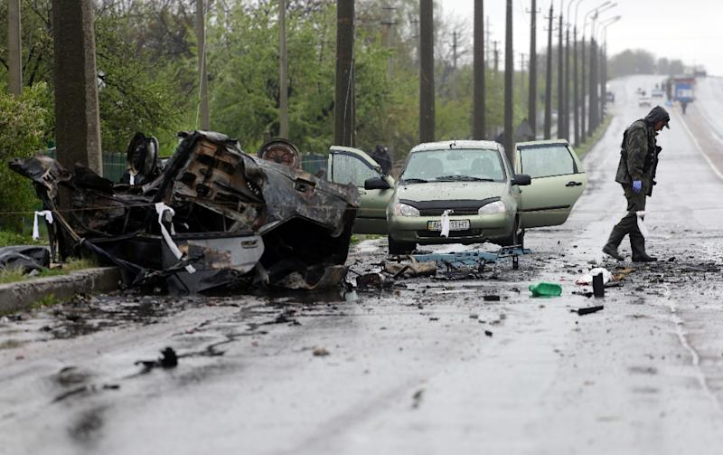 An expert examines a site where cars were destroyed by shelling at the rebel-controlled checkpoint in Olenivka, eastern Ukraine, on April 27, 2016