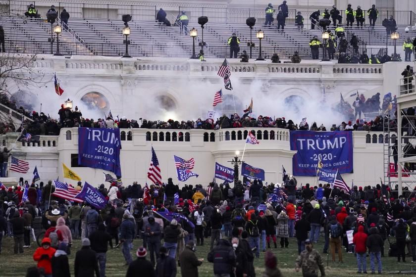 FILE - In this Jan. 6, 2021, file photo, violent protesters, loyal to then-President Donald Trump, storm the Capitol, Wednesday, Jan. 6, 2021, in Washington. Two Seattle police officers who were in Washington, D.C., during the January 6 insurrection were illegally trespassing on Capitol grounds while rioters stormed the building, but lied about their actions, a police watchdog said in a report released Thursday, July 8, 2021. (AP Photo/John Minchillo, File)