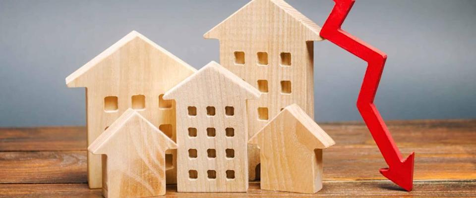 Miniature wooden houses and a red arrow down. The concept of lower mortgage interest rates.