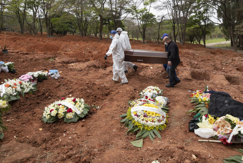 Cemetery workers in protective clothing and nephew Darick Caverni carry the coffin that contain the remains of 88-year-old Wilma Caverni, who died of the new coronavirus, at the Vila Formosa cemetery in Sao Paulo, Brazil, Wednesday, July 15, 2020. Brazil is nearing 2 million cases of COVID-19 and 75,000 deaths. (AP Photo/Andre Penner)