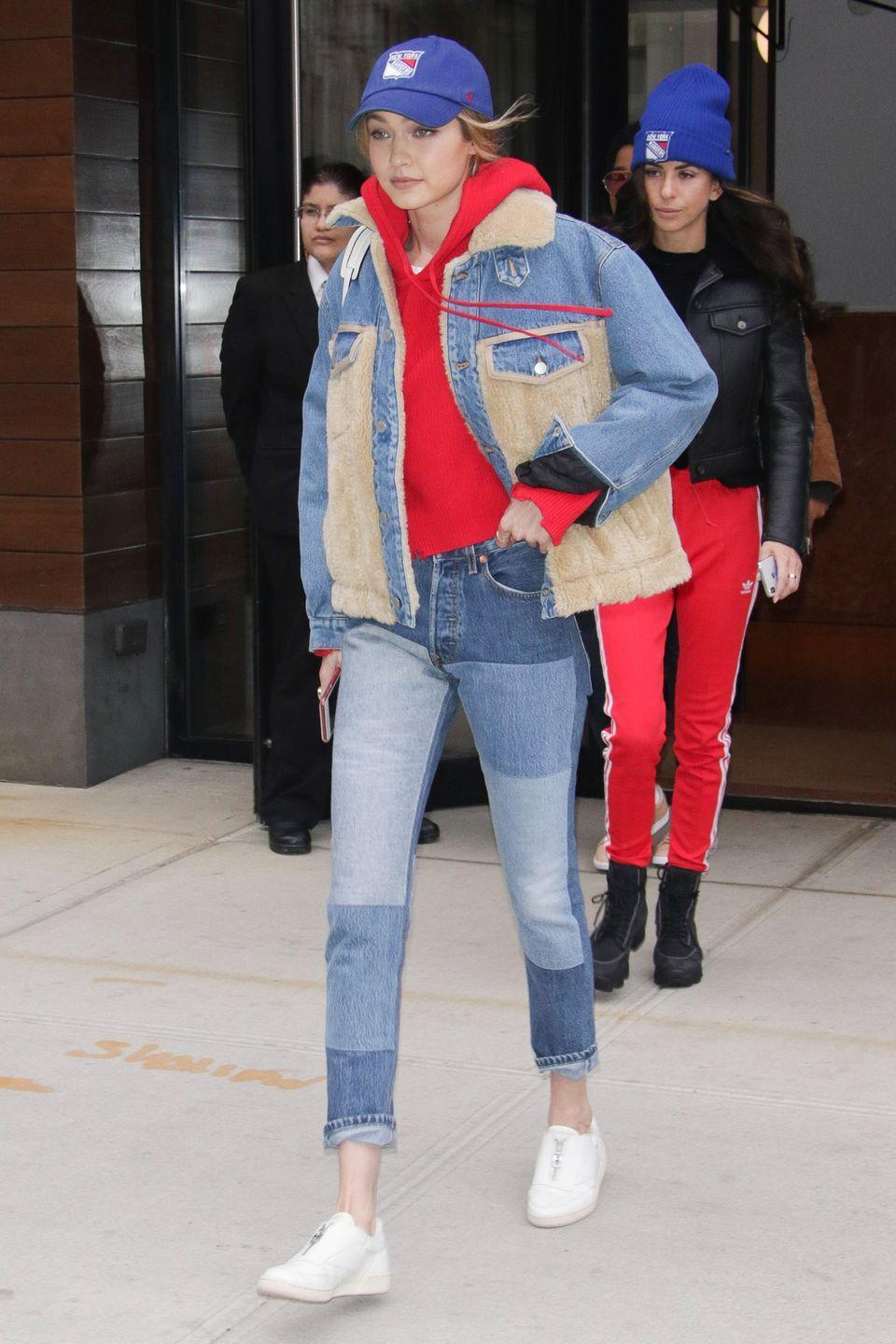 <p>In patchwork denim, a red sweatshirt under a denim and shearling coat, with a 'Rangers' baseball-style hat, and white sneakers while out in New York,</p>