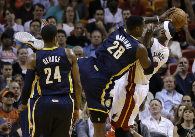 Miami Heat's LeBron James, right, is fouled by Indiana Pacers' Ian Mahinmi (28) during the first half of an NBA basketball game, Friday, April 11, 2014, in Miami. (AP Photo/Lynne Sladky)