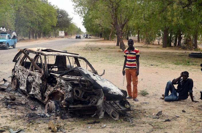 People stand by the wreckage of a car blown up by suspected Boko Haram militants in Nigeria's troubled northeastern city of Maiduguri on March 25, 2014, killing five police officers, while a separate blast killed three (AFP Photo/)