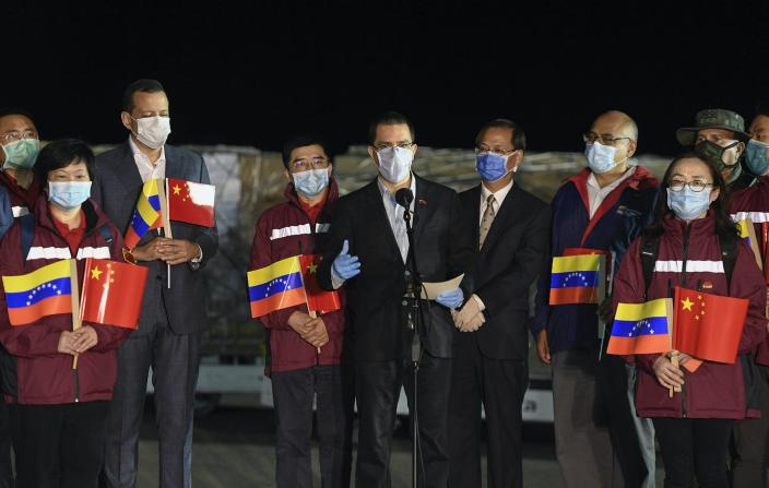 """<span class=""""caption"""">Venezuela Foreign Minister Jorge Arreaza, center, greets the arrival of medical specialists and supplies from China in March.</span> <span class=""""attribution""""><span class=""""source"""">AP Photo/Matias Delacroix</span></span>"""