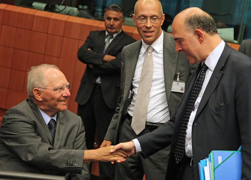 German Finance Minister Wolfgang Schaeuble, left, shakes hands with French Finance Minister Pierre Moscovici, during the Eurogroup meeting, at the European Council building in Brussels, Monday, July 8, 2013. The finance ministers of the 17 European countries that use the euro are expected to approve the release of another installment of the rescue funds that Greece has been relying on since May 2010. (AP Photo/Yves Logghe)