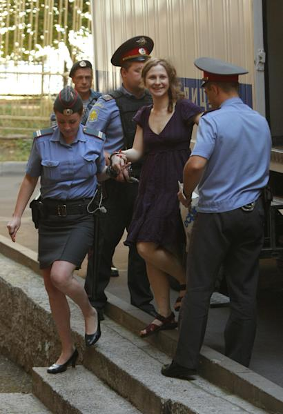Maria Alekhina, second right, a member of feminist punk group Pussy Riot is escorted to a court room in Moscow, Russia, Wednesday, Aug. 8, 2012. Prosecutors on Tuesday called for three-year prison sentences for feminist punk rockers who gave an impromptu performance in Moscow's main cathedral to call for an end to Vladimir Putin's rule, in a case that has caused international outrage and split Russian society.(AP Photo/Alexander Zemlianichenko)