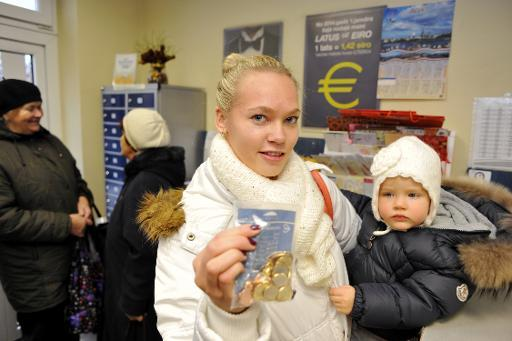 <p>Linda Grabouska shows an euro starter pack, containing a mixture of euro coins, she picked up with her daughter Jasmina at the Marupe post office near the Riga airport, on December 10, 2013</p>